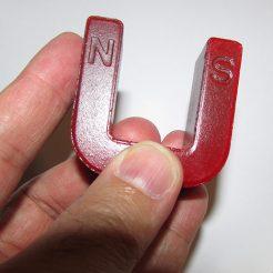 نمایی دیگر از قطب های آهنربای یو شکل که بروی آن حروف N و S حک شده است